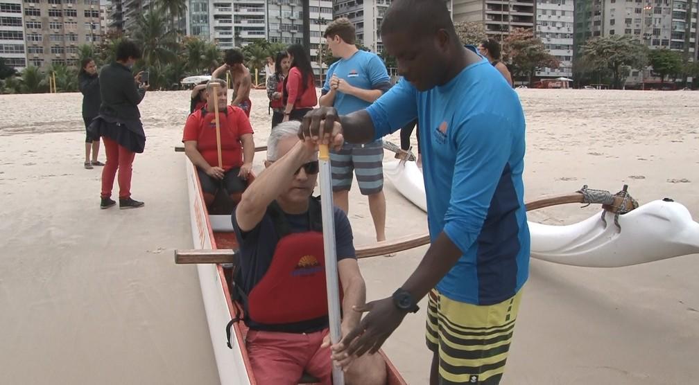 Profissionais auxiliam os deficientes visuais a maneira correta de remar na canoa. (Foto: Miguel Folco / G1)