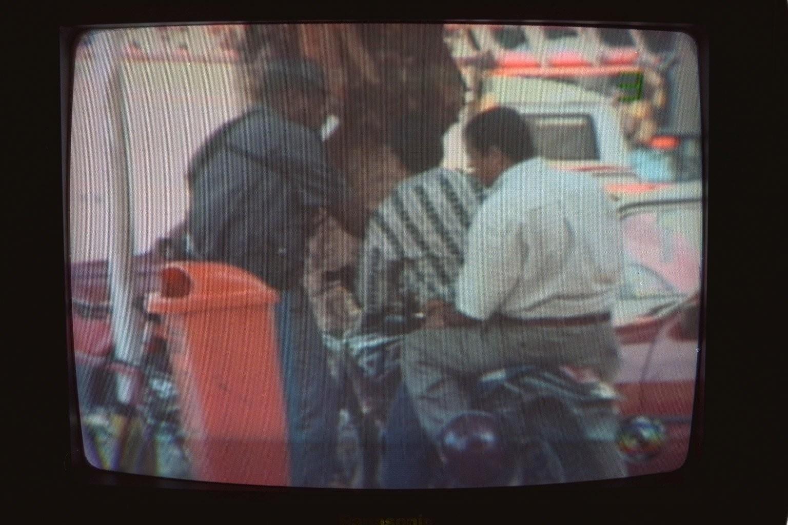 O policial usa a mão direita para revistar o suspeito sentado à frente da moto
