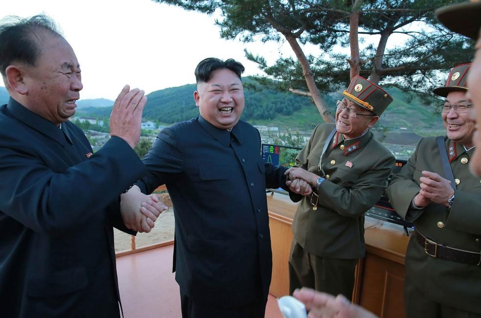 O ditador norte-coreano Kim Jong-un reage com alegria entre autoridades do seu governo durante teste de lançamento de um míssil terra-terra Hwasong-12 em local não revelado. A foto da véspera foi divulgada nesta segunda-feira (15) (Foto: AFP/KCNA via KNS)