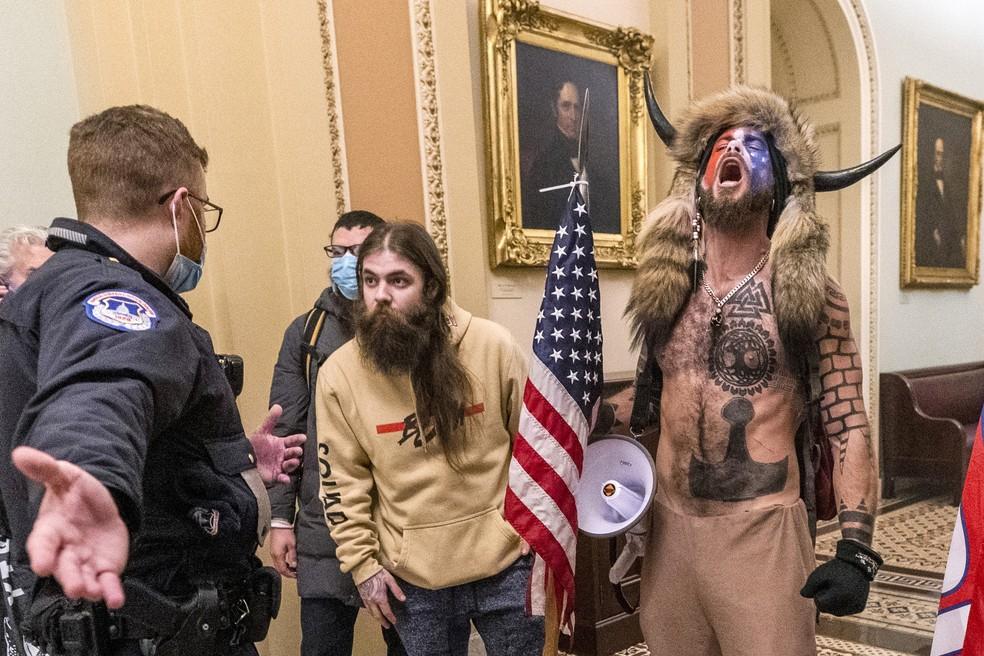 Foto de 6 de janeiro de 2021, dia da invasão ao Capitólio dos EUA, mostra policiais conversando com apoiadores do então presidente americano, Donald Trump, incluindo Jacob Chansley (à direita), do lado de fora do plenário do Senado — Foto: Manuel Balce Ceneta/AP