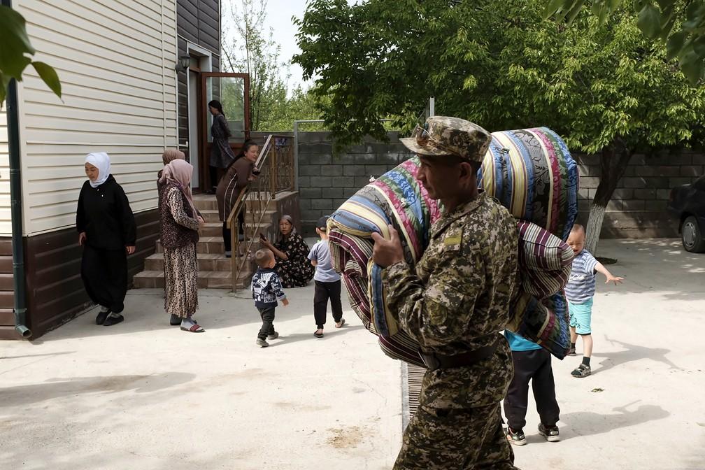 Funcionário fardado do governo quirguiz carrega colchões para moradores de área na fronteira entre Quirguistão e Tajiquistão evacuada pelos conflitos entre os dois países nesta sexta (30) — Foto: Stringer/AFP