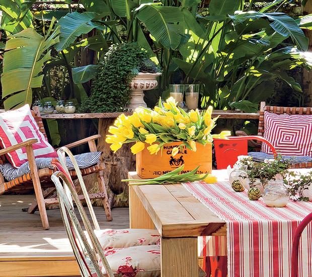 Utilizada para refeições mais demoradas e especiais, a mesa de jantar da área externa tem cadeiras de latão com almofadas florais. A caixa de vinho virou cachepô para as tulipas. Casa da produtora de eventos Lica Paludo (Foto: Lufe Gomes)
