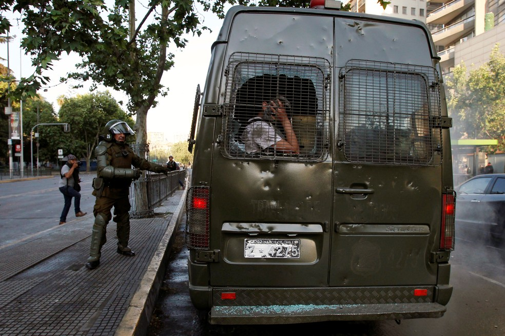 Manifestante é detido pela polícia de choque durante ato em Santiago — Foto: Reuters/Carlos Vera