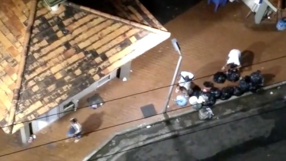 Jovens pegando garrafas no lixo para jogar na polícia (Foto: Reprodução/ TV Gazeta)