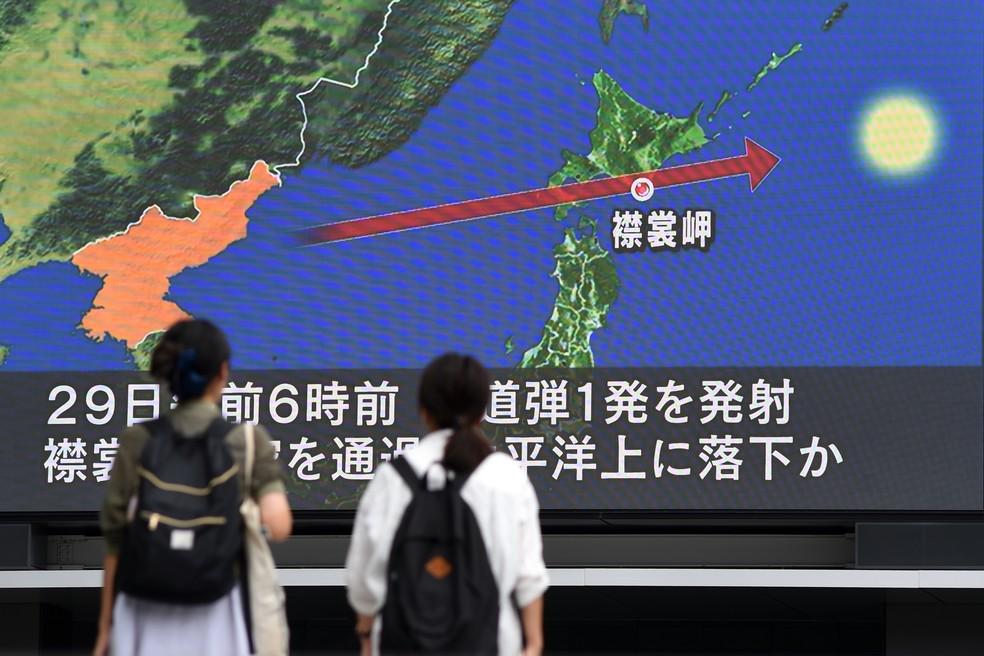 Pedestres assistem à notícia sobre o lançamento de um míssil que sobrevoou o Japão, nesta terça-feira (29) em Toquio (Foto: Toshifumi KITAMURA / AFP)