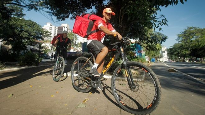 Os entregadores Robert dos Santos, 23, e Gabriel de Jesus, 22, trabalhando em Pinheiros, zona oeste de São Paulo (Foto: LINCON ZARBIETTI, via BBC News Brasil)