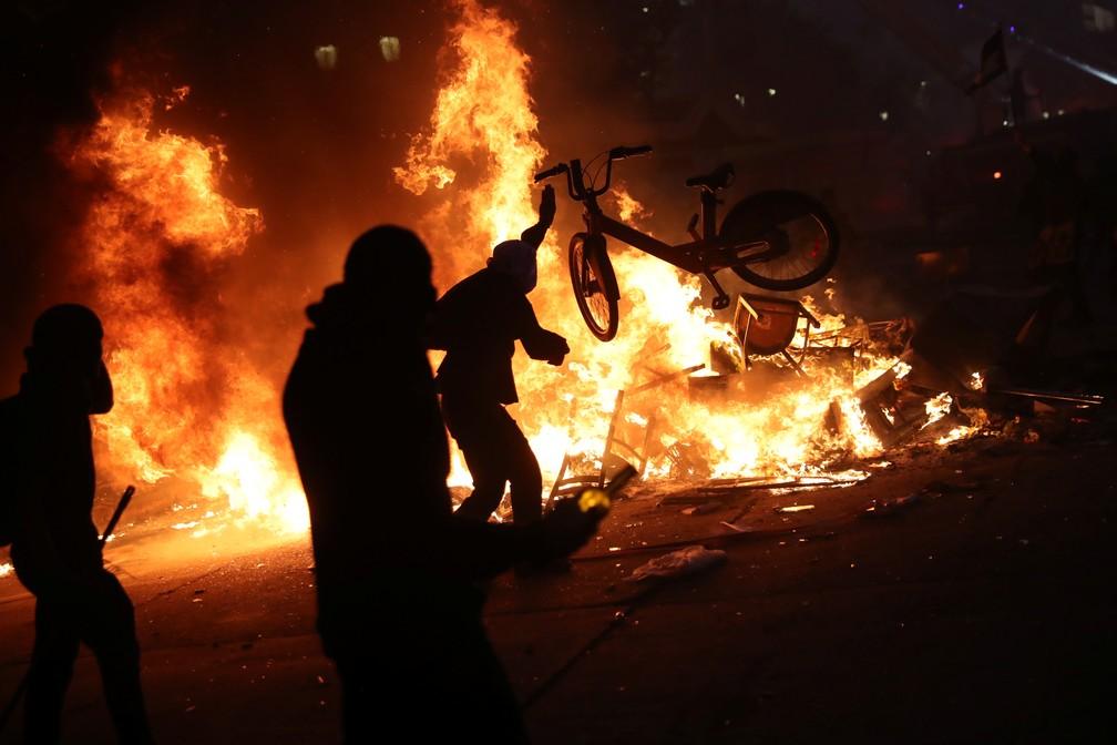 Manifestante joga bicicleta em fogueira de barricada em Santiago, no Chile, nesta segunda-feira (28) — Foto: Edgard Garrido/Reuters