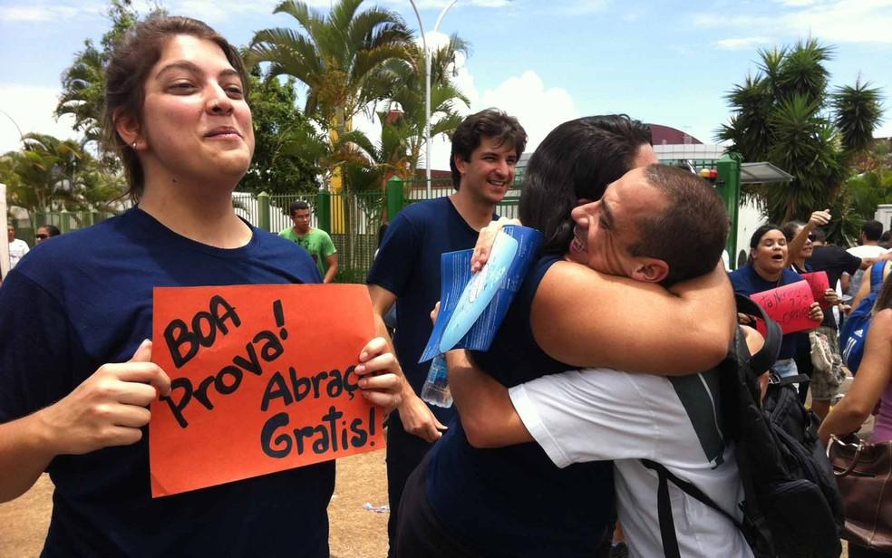 Enquanto colega abaça candidato, garota segura cartaz em que oferece abraço grátis aos estudantes que fazem prova do Enem neste domingo em Brasília — Foto: Natalia Godoy/G1