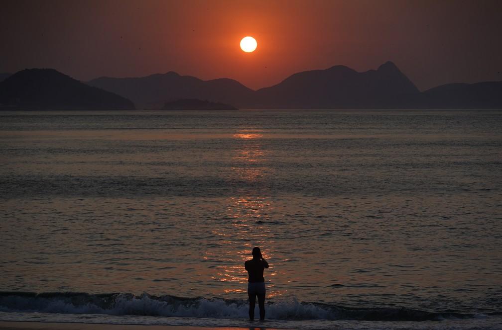 Homem entra na água para registrar o nascer do sol no dia que pode ser o mais quente do ano no Rio — Foto: Marcos Serra Lima/G1