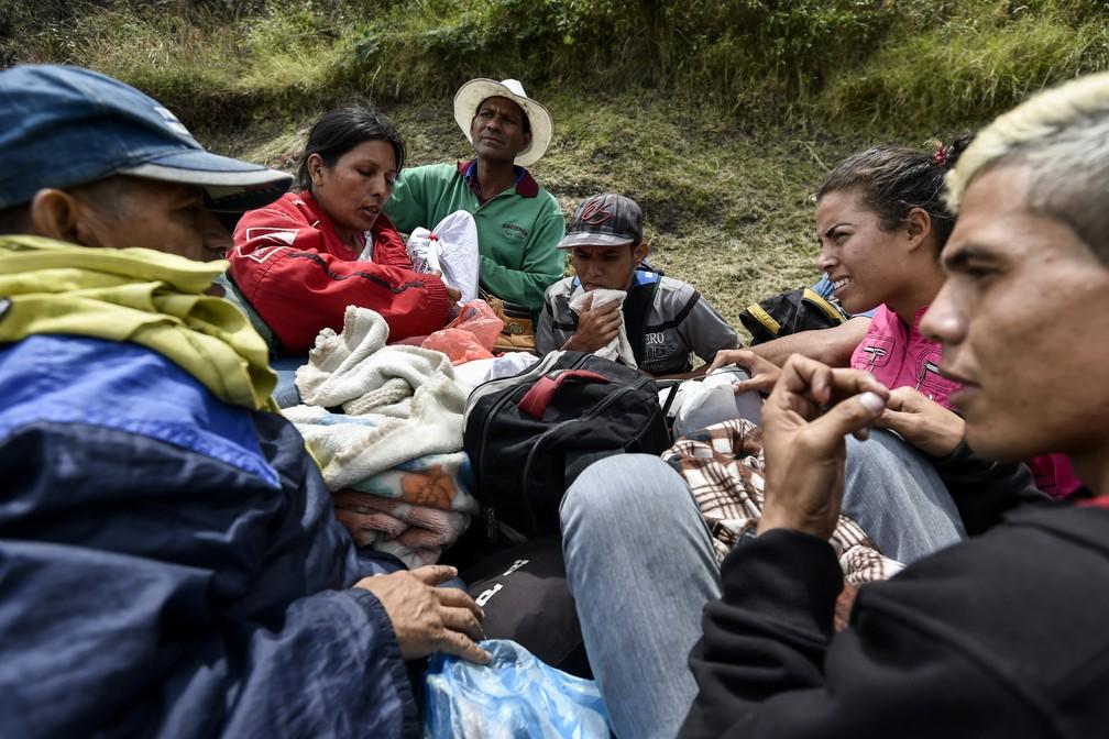 Imigrantes venezuelanos viajam em caçamba de caminhonete pela estrada Panamericana, na Colômbia (Foto: Luis Robayo/ AFP)