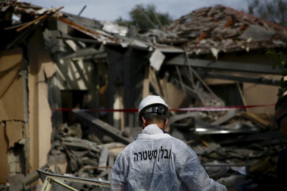 Policial israelense inspeciona casa atingida por foguete em Mishmeret, na região central de Israel, nesta segunda-feira (25) — Foto: Ariel Schalit/AP