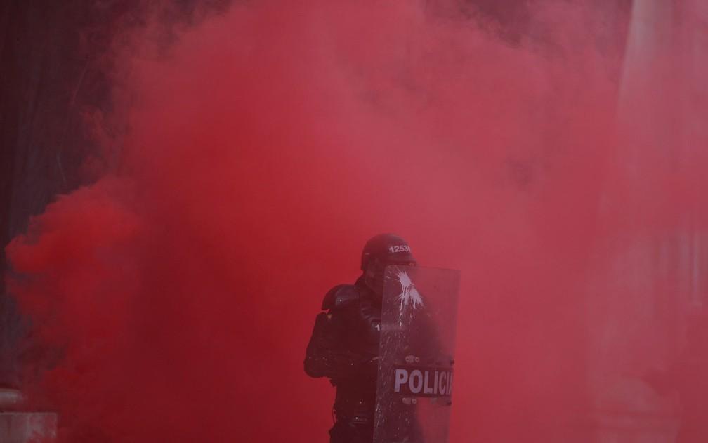 Policial é visto em meio a fumaça de gás lacrimogêneo dur — Foto: AP Photo/Fernando Vergara