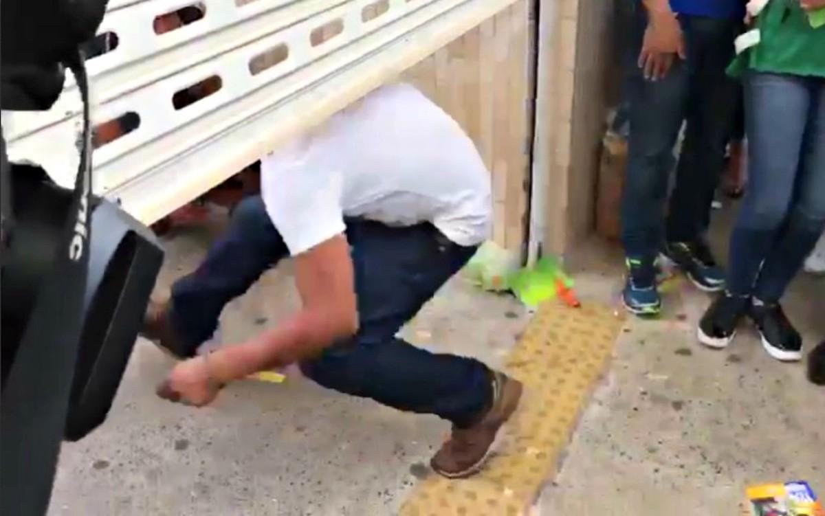 Candidato atrasado se agacha para entrar em local de prova de Cuiabá