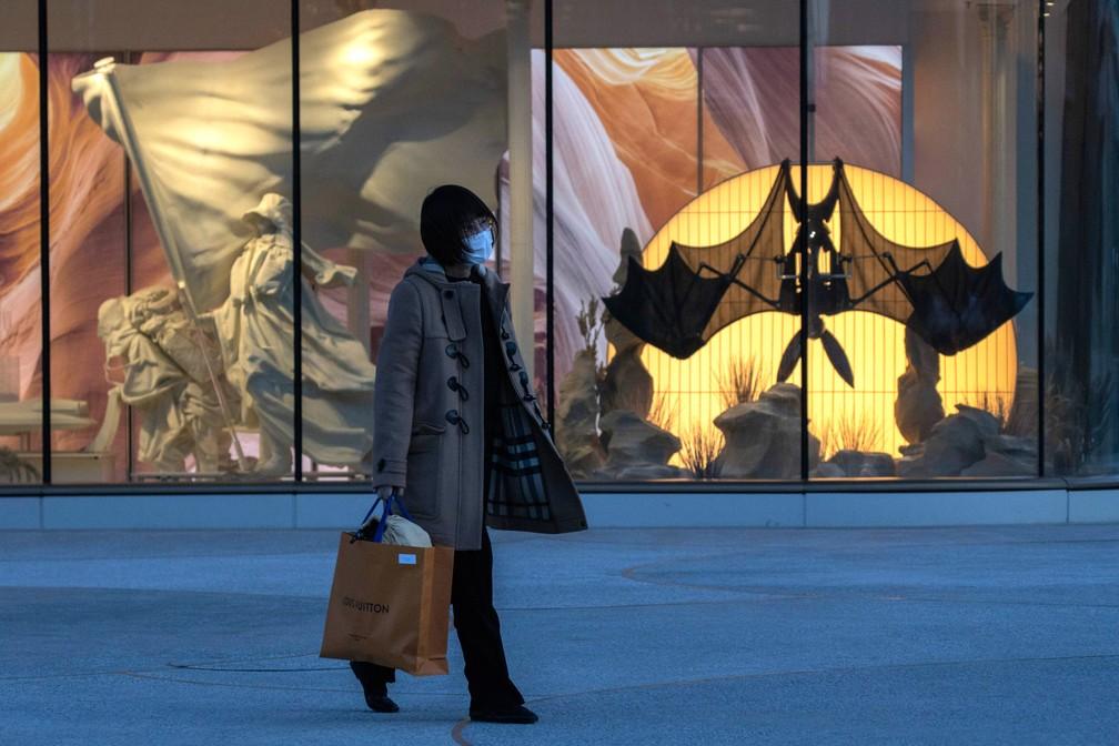 Uma mulher caminha em frente à vitrine de uma loja em Pequim, neste domingo (15). A China intensificou controles sobre viajantes internacionais no aeroporto de Pequim e disse que colocará em quarentena todos que chegarem à capital do país — Foto: Nh Han Guan/AP