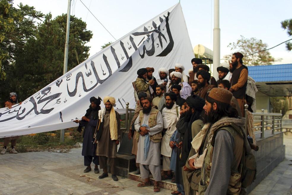 Talibãs com a bandeira de seu grupo na residência do governador da província de Ghazni, em 15 de agosto de 2021 — Foto: Gulabuddin Amiri/AP