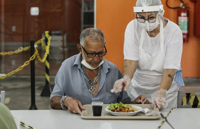 NITEROI, BRAZIL - AUGUST 05: An employee wearing a face mask serves food on a table with alternating spaces at a popular soup kitchen on August 5, 2020 in Niteroi, Brazil. Employees received special training to ensure the safety of visitors. The site will (Foto: Getty Images)