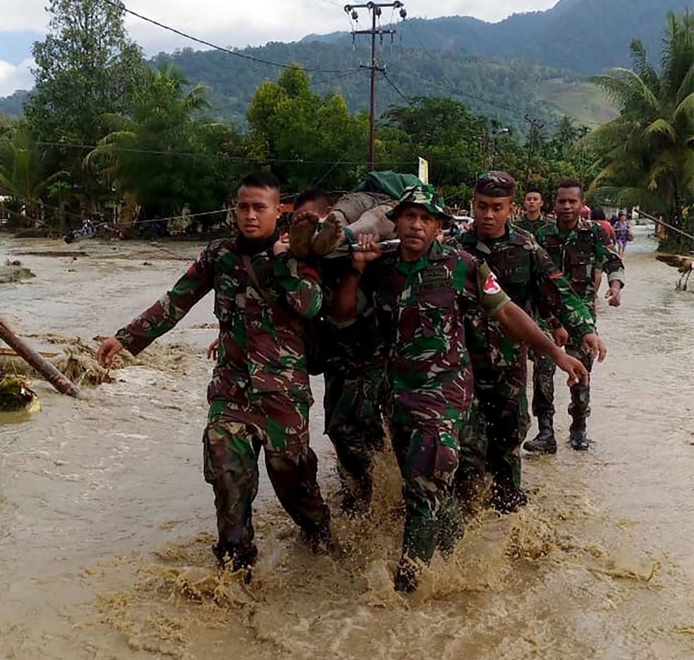 Militares da Indonésia retiram vítima de enchente em Sentani, em Papua, neste domingo (17) — Foto: Exército da Indonésia / AFP