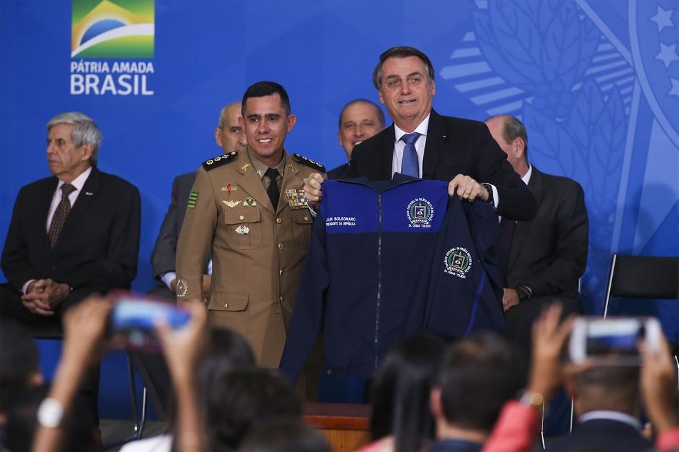O Presidente Jair Bolsonaro mostra casaco que recebeu de presente durante o lançamento do Programa Nacional das Escolas Cívico-Militares (Pecim), em Brasília. No evento, ele defendeu a imposição das escolas cívico-militares para as pessoas não dependerem de programas sociais 'até morrer' — Foto: Antonio Cruz/Agência Brasil
