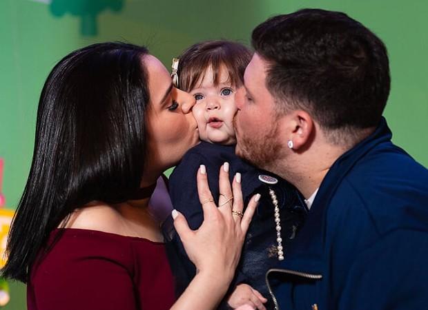 Ferrugem e a mulher, Thais Vasconcelos, dão beijo-sanduíche na filha Sofia (Foto: Chris Machado)