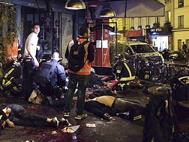 Corpos de mortos em ataque a tiros no restaurante La Belle Equipe são vistos entre mesas, com sangue na calçada em frente ao estabelecimento em Paris (Foto: Anne Sophie Chaisemartin via AP)