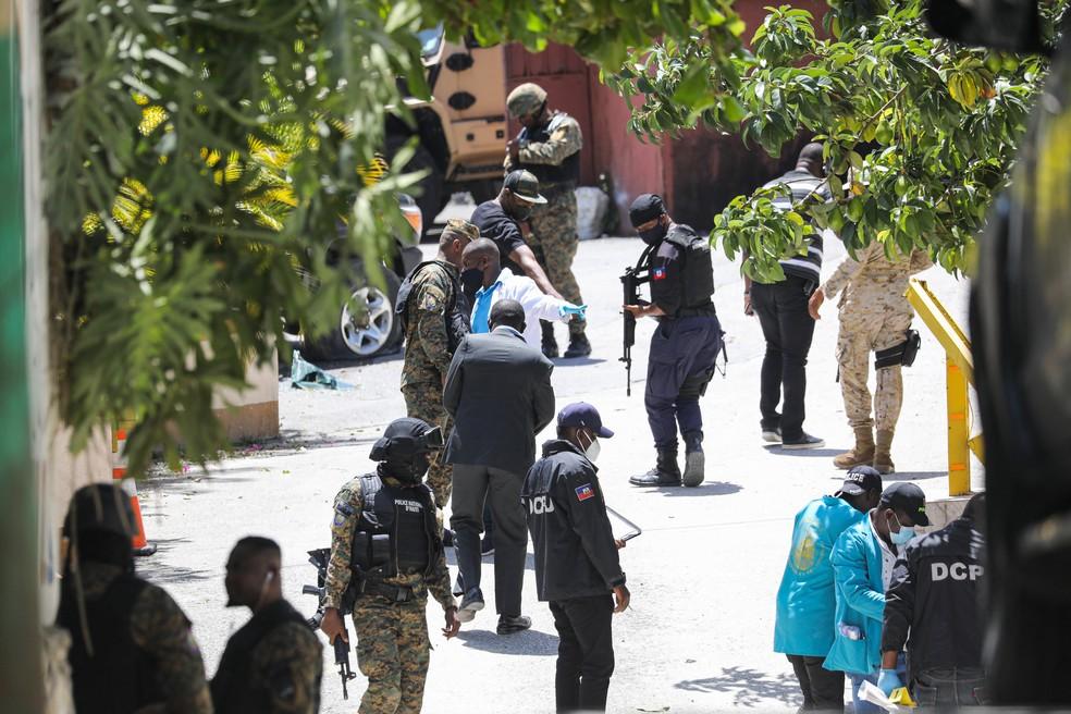 Membros da polícia haitiana procuram evidências fora da residência presidencial em Porto Príncipe, em 7 de julho de 2021, onde o presidente do Haiti, Jovenel Moise, foi assassinado a tiros na madrugada — Foto: Valerie Baeriswyl/AFP