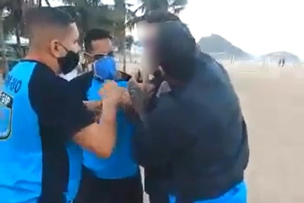 Guardas tentam imobilizar homem que resiste a abordagem na Praia de Copacabana — Foto: Reprodução