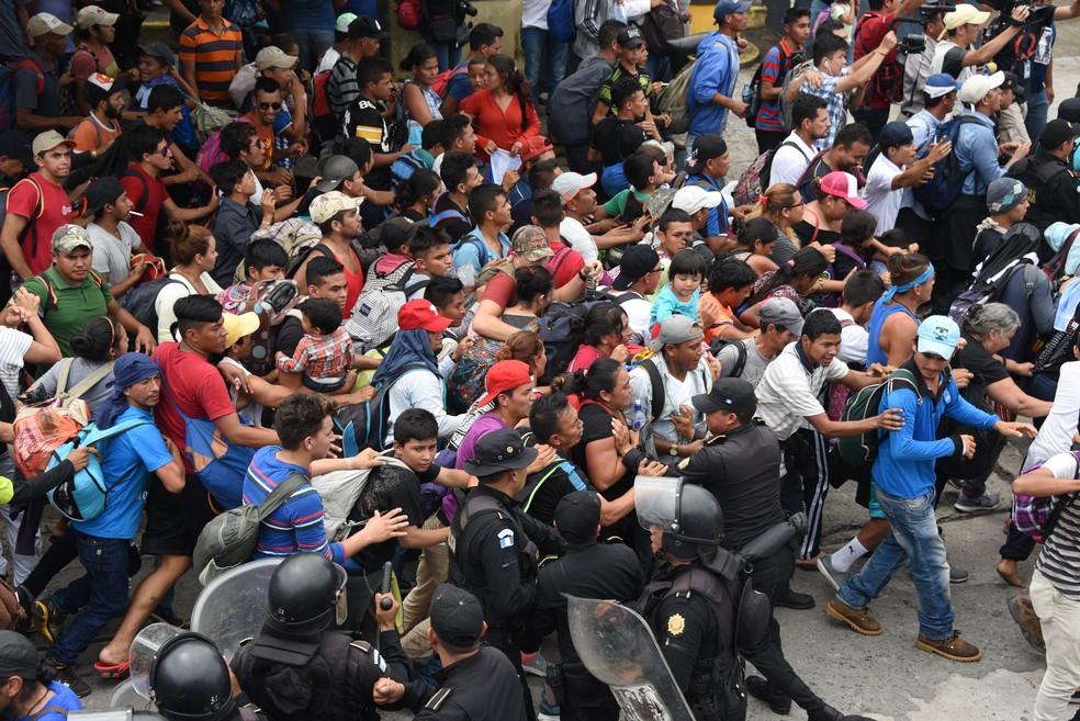 Imigrantes hondurenhos passam por bloqueio policial em Ciudad Tecun Uman ao atravessar a fronteira da Guatemala com o México nesta sexta-feira (19) — Foto: Johan Ordonez/ AFP
