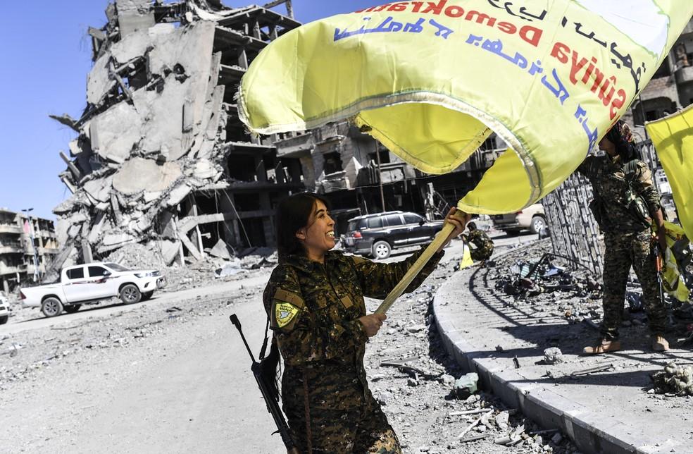 Comandande do conglomerado árabe-curdo Forças Democráticas da Síria (FDS) comemora em praça de Raqqa, na Síria, vitória sobre o grupo Estado Islâmico — Foto: Bulent Kilic/AFP
