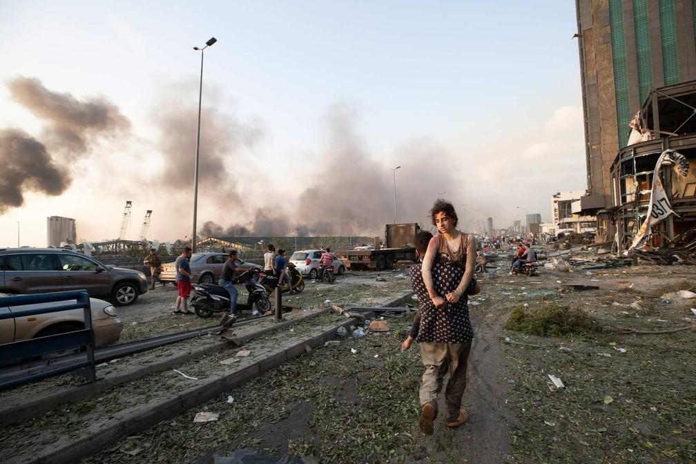 Homem carrega ferida em explosão em Beirute; testemunhas dizem que muitas pessoas ficaram feridas por detritos e vidros arremessados pela explosão. — Foto: Hassan Ammar/AP
