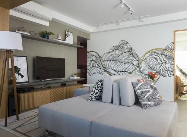 A área da sala reservada para a TV tem pintura em tom de cinza numa das paredes, contrastando com o grafite na outra  (Foto: Manu Oristânio/Divulgação )