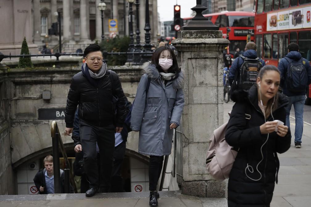 Uma mulher com uma máscara protetora é vista saindo do metrô de Londres, no Reino Unido, nesta quarta (4). A feira do livro da cidade foi cancelada por causa do Covid-19, doença causada pelo novo coronavírus. — Foto: Matt Dunham/AP