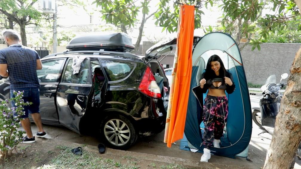 Modelo usa barraca para fazer troca de looks durante ensaio em frente a mansões do Jardim Europa — Foto: Marcelo Brandt/G1