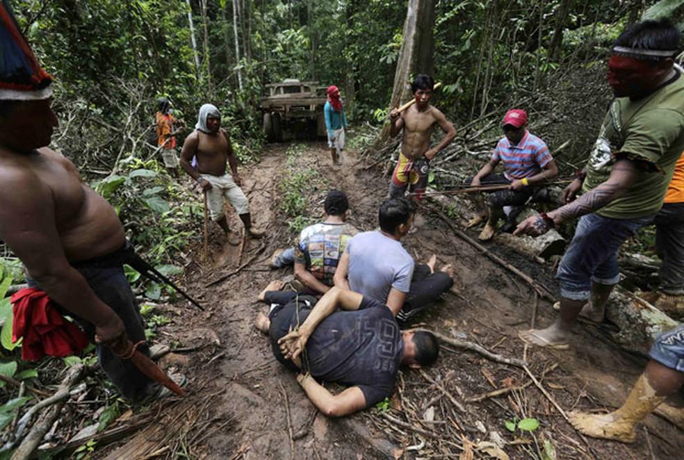 Indígenas cercam homens que estavam em acampamento montado na Terra Indígena Alto Turiaçu, com a finalidade de desmatar a região — Foto: Lunae Parracho/Reuters