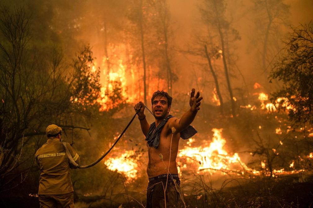 Residente local gesticula enquanto segura mangueira de água vazia em tentativa de extinguir incêndios florestais na Grécia, neste domingo (8) — Foto: Angelos Tzortzinis/AFP