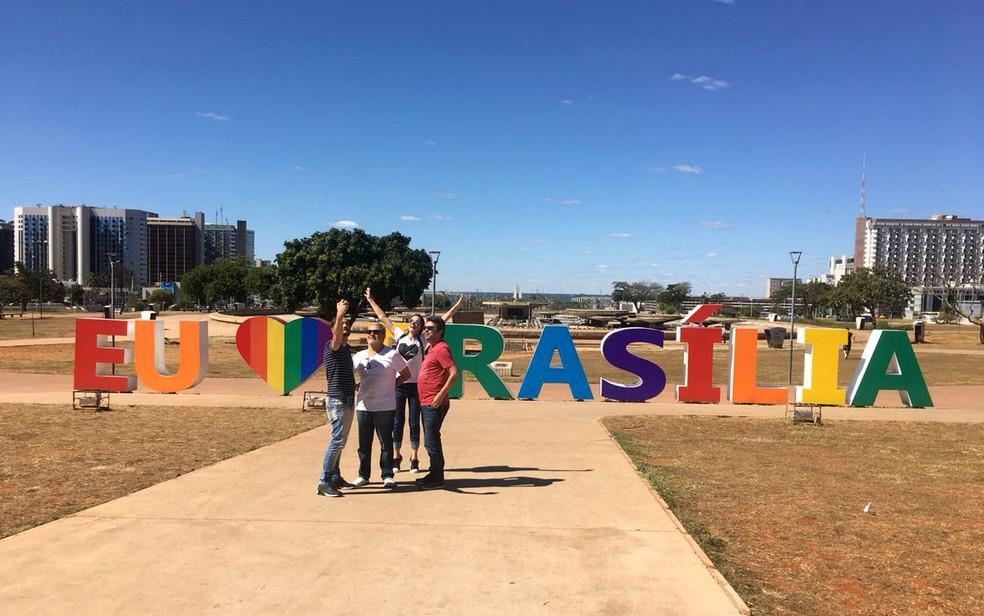 Turistas tiram foto em frente a escultura em homenagem a Brasília com cores da bandeira LGBT (Foto: Luiza Garonce/G1)
