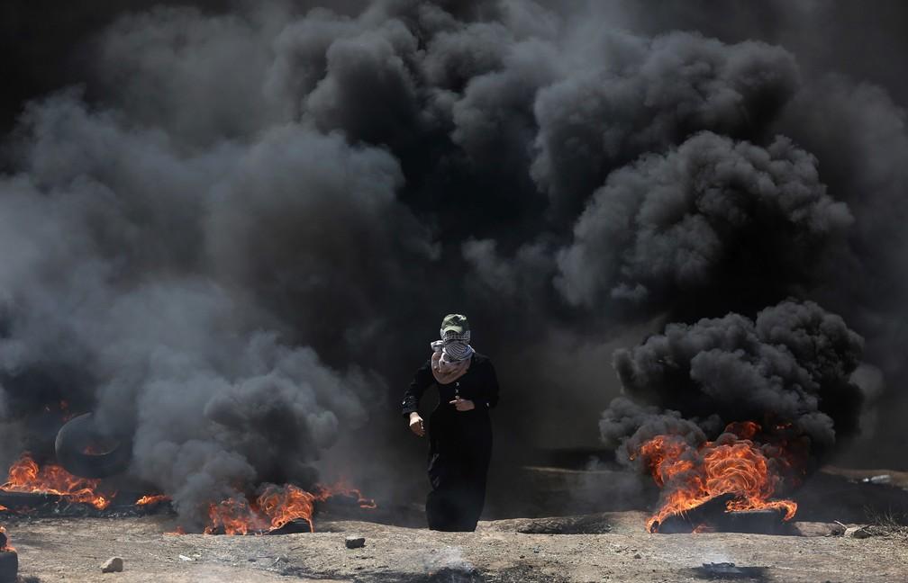 Uma mulher palestina caminha por uma nuvem de fumaça negra de pneus em chamas durante um protesto na fronteira entre Gaza e Israel contra a inauguração da embaixada dos EUA em Jerusalém (Foto: Khalil Hamra/AP)