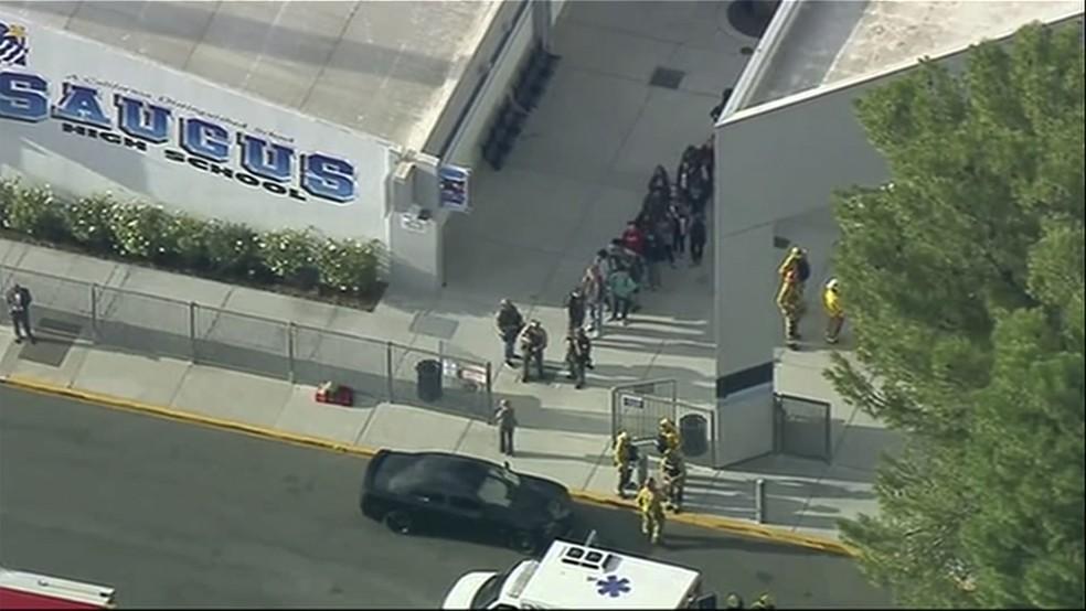 Pessoas são tiradas da escola de ensino médio de Saugus, em Santa Clarita, na Califórnia, depois de um tiroteio nesta quinta (14). — Foto: KTTV-TV via AP