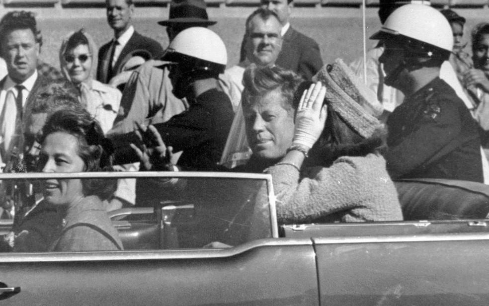O presidente dos EUA John F. Kennedy acena de seu carro em 22 de novembro de 1963, ao lado da primeira-dama Jacqueline Kennedy, pouco antes de ser assassinado (Foto: AP Photo/Jim Altgens)