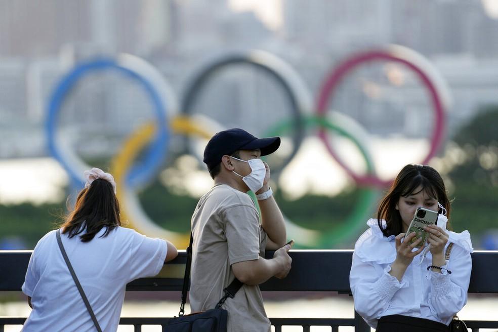 Pessoas passam em frente aos anéis olímpicos em Tóquio, no Japão, no domingo (25) — Foto: Eugene Hoshiko/AP Photo