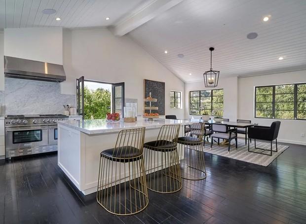 O branco da cozinha contrasta com as banquetas e móveis escuros (Foto: The Agency)