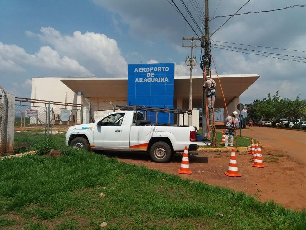 Funcionários da concessionária de energia religando a eletricidade (Foto: Cássia Rangel/TV Anhanguera)