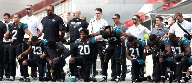 Jogadores do Jacksonville Jaguars, em jogo contra os Baltimore Ravens pela NFl, se ajoelham durante execução do hino americano  (Foto: Paul Childs / Action Images via Reuters / O Globo)