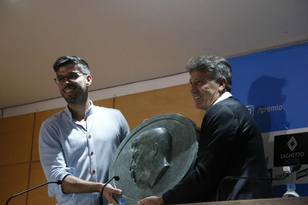 Renato ganha do artista Theo Felizzola o medalhão que também está na estátua — Foto: Eduardo Moura