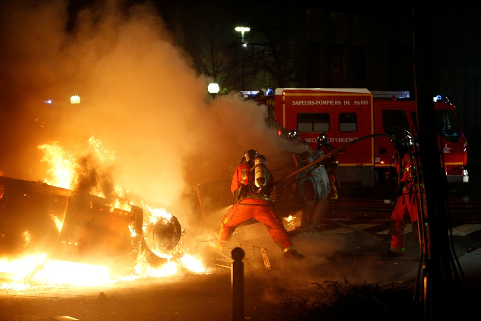Bombeiros tentam apagar chamas de carro após protesto em Paris — Foto: REUTERS/Stephane Mahe