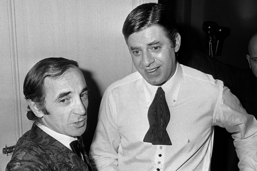 Nesta foto de arquivo tirada em 15 de abril de 1971 o cantor e ator Charles Aznavour (L) parabeniza o comediante, diretor e cantor norte-americano Jerry Lewis em seu camarim após seu show no L'Olympia em Paris. — Foto: AFP