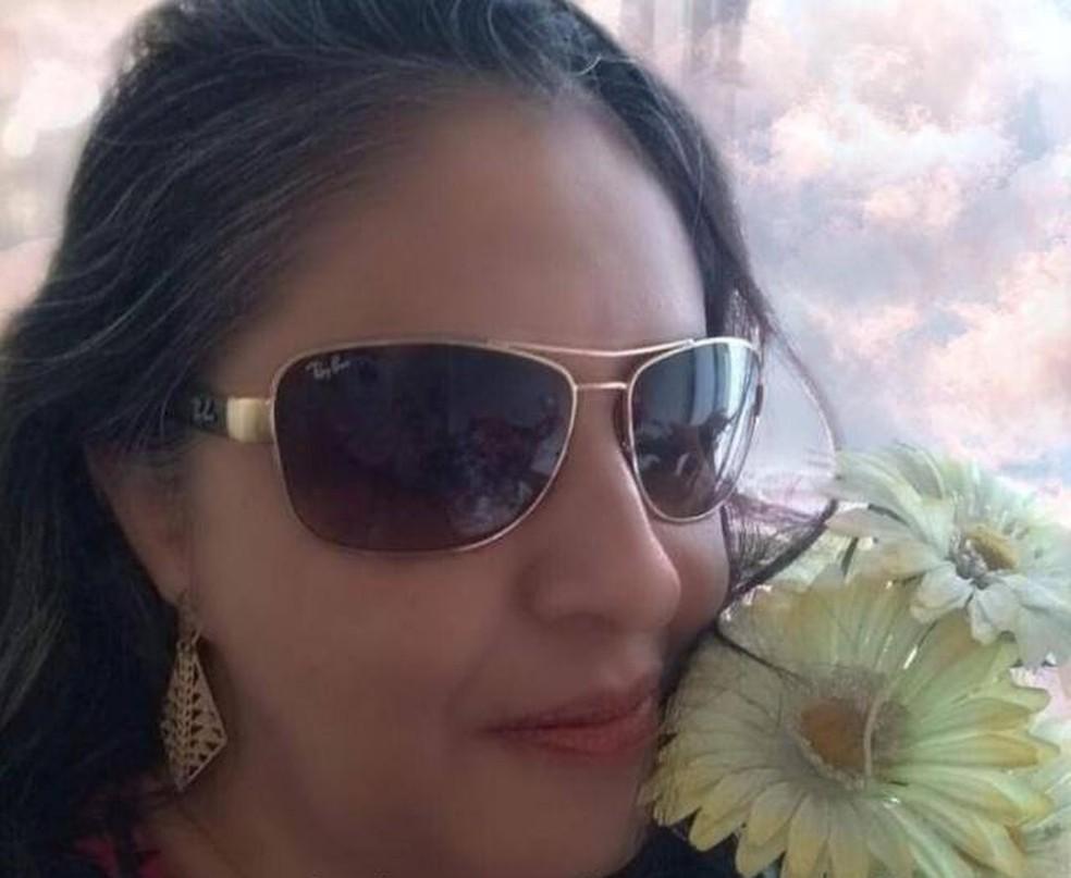 Marinalva Lopes tem deficiência visual. Na foto, ela está séria, de óculos escuros, com duas flores perto do rosto. — Foto: Marinalva Lopes/Arquivo pessoal