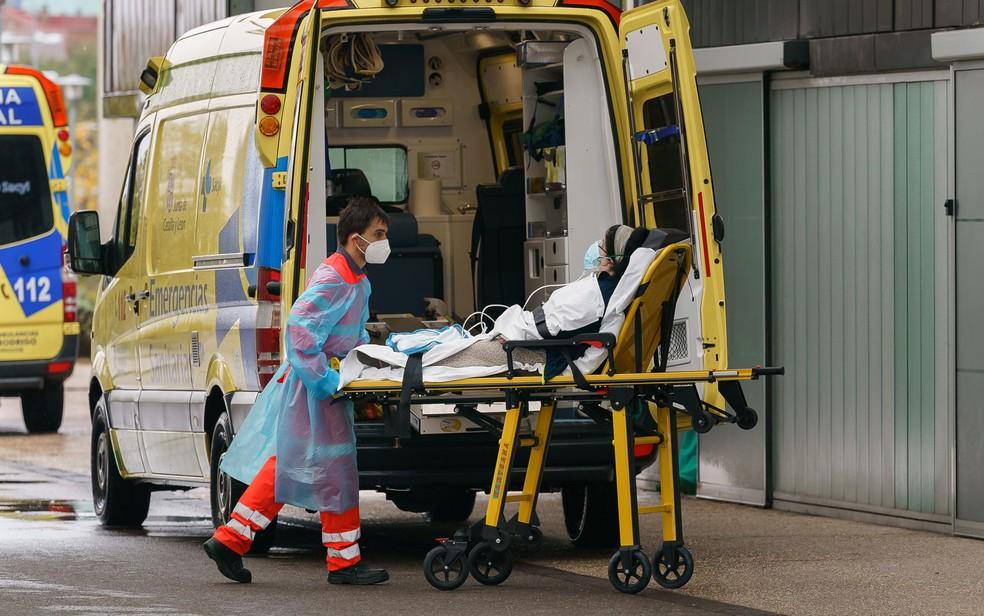 Paramédico retira mulher de uma ambulância na entrada de hospital em Burgos, na Espanha, na quarta-feira (21)  Foto: Cesar Manso/AFP