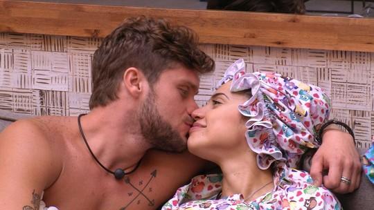 Paula e Breno trocam beijinhos no sofá, ao lado de Jéssica
