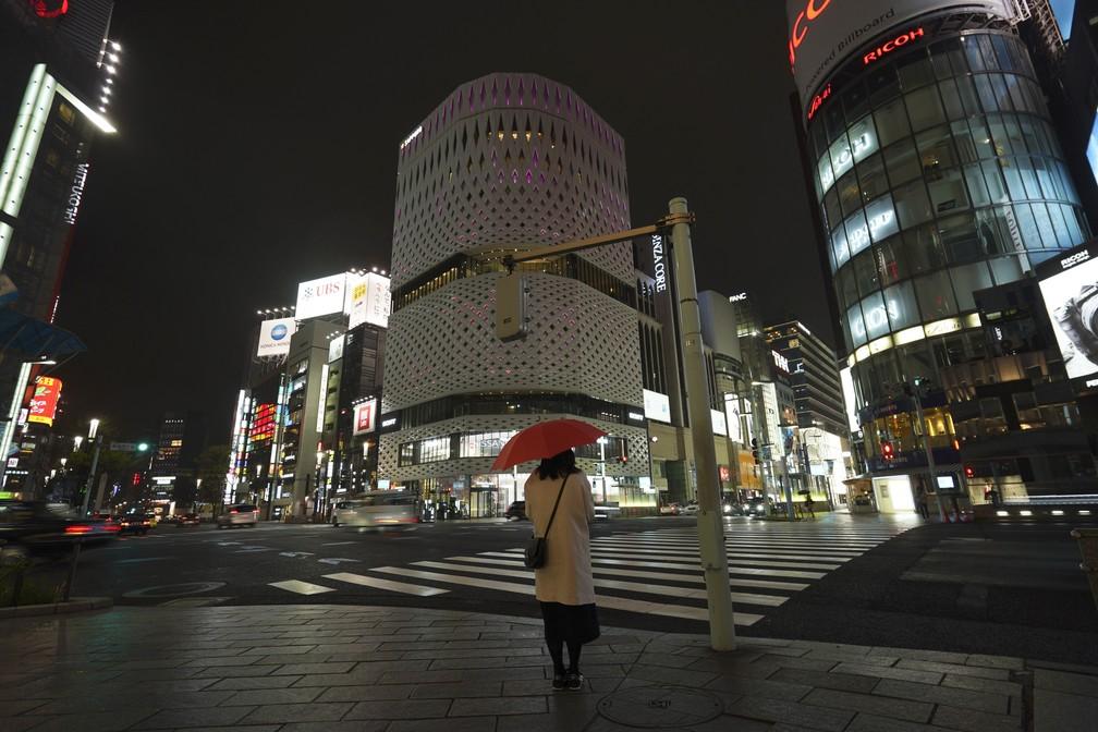 Tóquio, no Japão, com apenas uma mulher na rua à noite: cidade vive os efeitos da pandemia — Foto: Eugene Hoshiko/AP Photo