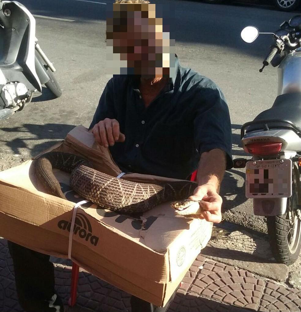 Foto mostra ambulante manuseando cobra em frente a bar em São Vicente, SP (Foto: G1 Santos)